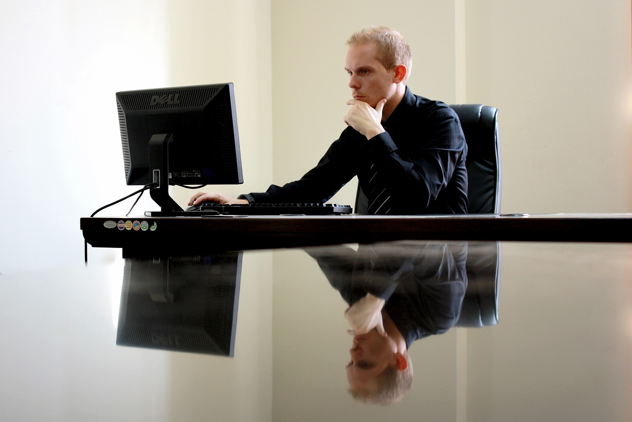 man looking at computer screen contemplating